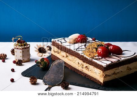 Christmas cake with fresh strawberries, whipped cream, chocolate and walnuts on black slate cake board on blue background with christmas decorations, fir cones, gift, holly tree and berry