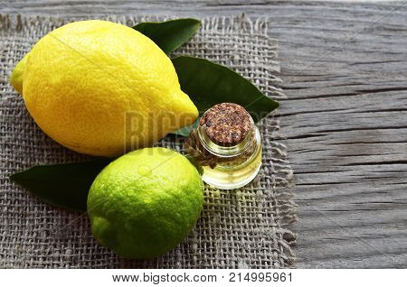 Lemon essential oil in a glass bottle with fresh lemon and lime fruits.Lemon oil for spa,aromatherapy and bodycare.Extract oil of lemon.Selective focus.
