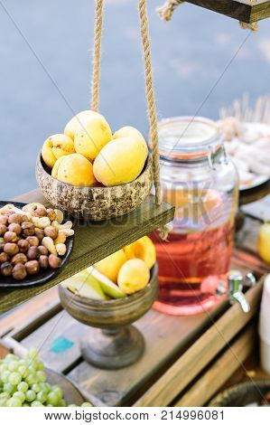 small business, creating, vegetarian concept. close up of fresh mellow fruits and nuts on the dark colored wooden shelves of grocery shop, where everybody can buy some confection or drink