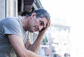 close up portrait of sad and depressed 40s man looking through outdoors at home balcony lonesome and thoughtful suffering depression thinking and feeling low in city buildings urban background poster