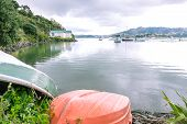 Orange clinker rowing dinghy with boats moored in Whangaroa Harbour Far North District Northland New Zealand NZ in background poster