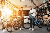 A seller at a bicycle store helps a young buyer choose a new mountain bike. A man with a beard and a client looks carefully at the goods. Around them there are many parts for bicycles. poster