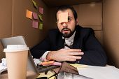 exhausted businessman with sticky note on forehead in box poster