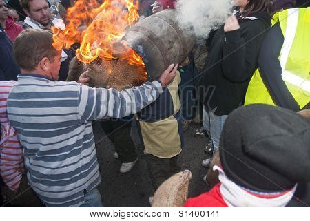 Carnival Committee Members Helps A Young Roller  To Pick Up A Burning Tar Barrel At The Start Of The