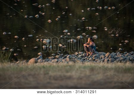 Riomalo De Abajo, Extremadura, Spain - July 13, 2018: A Woman Sitting On The Rounded Stone Of The Al