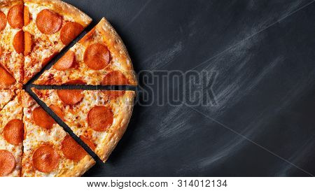 Tasty Pepperoni Pizza And Cooking Ingredients Tomatoes Basil On Black Concrete Background. Top View