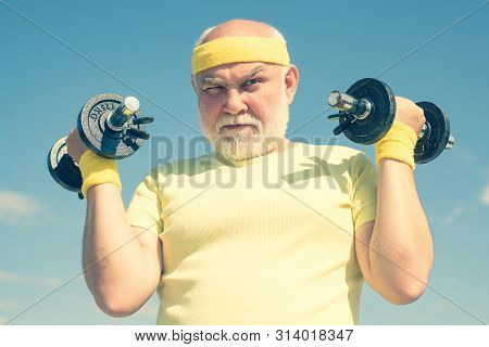 Senior Man Workout In Rehabilitation Center. Lifting Dumbbells. Health Club Or Rehabilitation Center