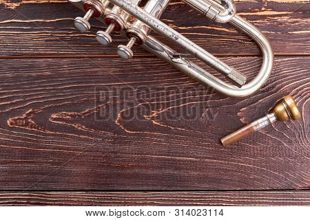 Old Trumpet On Wooden Background. Vintage Silver Trumpet And Copy Space. Brassy Trumpet Mouthpiece.