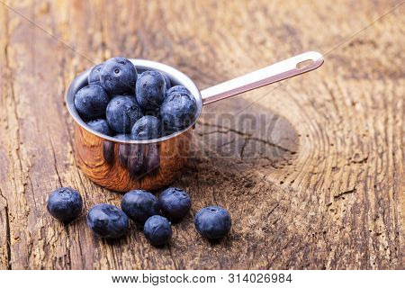 Blue Berries In A Pot On Wood