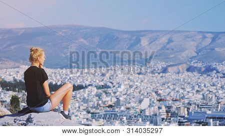 Young Tourist Woman Sitting On Top Of Mountain And Looking At A Beautiful Landscape Cityscape Athens
