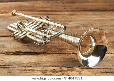 Rusty Trumpet On Old Wooden Surface. Antique Trumpet On Rustic Boards. Classical Jazzy Instrument.