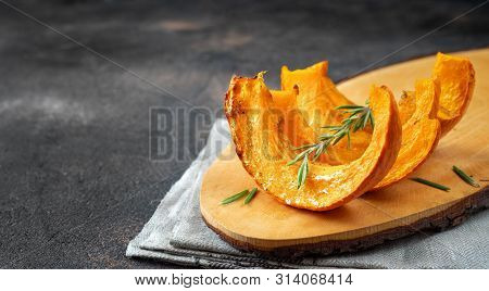 Slices Of Roasted Pumpkin On Wooden Tray And Dark Background