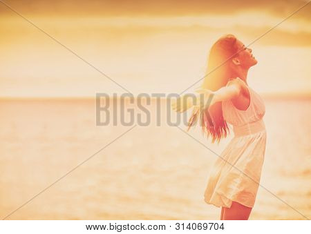 Wellness woman feeling free with open arms in freedom side profile silhouette on ocean beach background. Stress free happy emotion people.