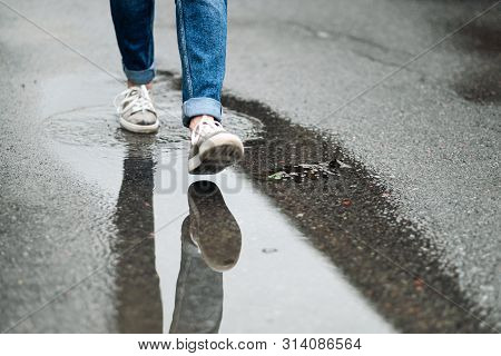 Close-up Of Feet In Sneakers Are Walking Through The Puddles On The Pavement.