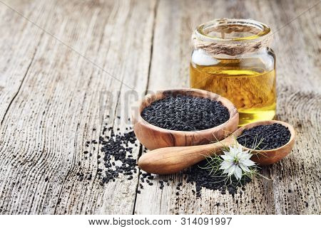 Black cumin oil with seeds and flower nigella sativa on wooden background