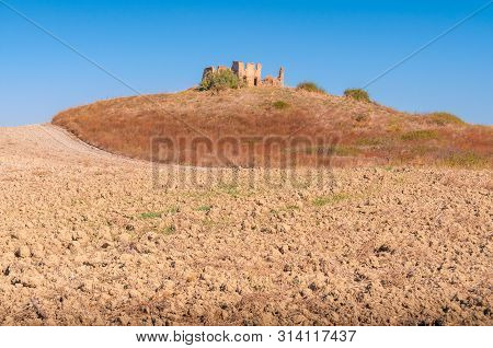 Arid Landscape With Barren Land And Parched Earth With Ruins Of Farmhouse In The Distance. Global Wa