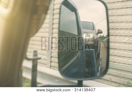 View From Car Side Mirror Of Tow Truck Towing A Broken Down Car On The Highway