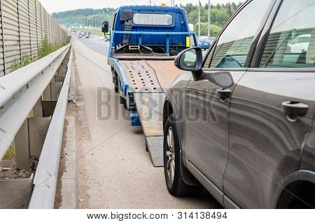 Tow Truck Towing A Broken Down Car On The Highway
