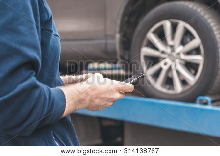 Man With Mobile Phone.tow Truck With Worker Towing A Broken Down Car On The Highway. Selective Focus