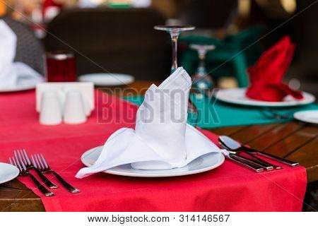 Nicely Decorated Table Appointments With Beautiful Decor With Plates And Serviettes. The Elegant Din