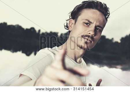 Portrait Of A Brutal Stylish Guy Aggressively Looking Into The Camera. Black And White Photo. Selfie