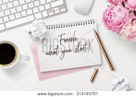 finish what you start - business concept. Notepad / ring binder, crumpled paper balls, mug with coffee and office supplies on a white feminine styled desktop, top view