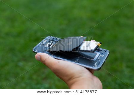 Close Up Of A Damaged Smartphone With Expanded Lithium Ion Battery