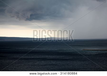 Supercell Storm With Dramatic Dark Cloud And Rainstorm At The Sea