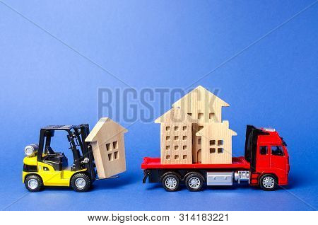 A Yellow Forklift Loads A House Figures On A Red Truck. Concept Of Transportation And Cargo Shipping