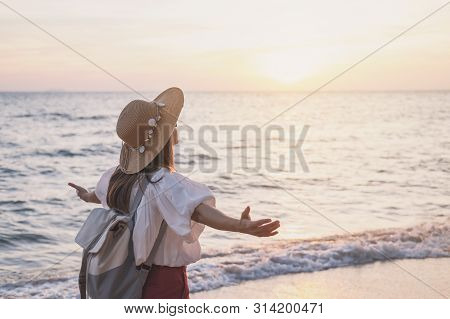 Young Traveler Woman Relaxing On Tropical Beach At Sunset, Vacation And Summer Concept
