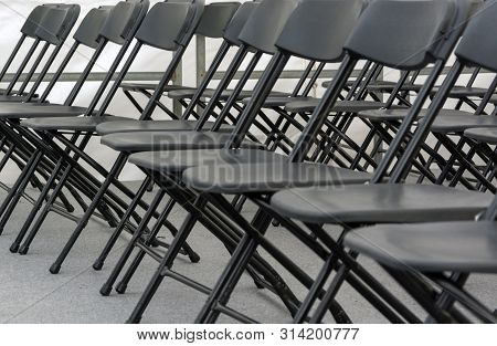poster of numerous folding chairs arranged in a row in a conference room.