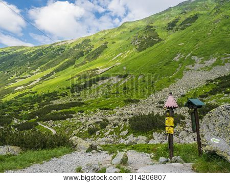 Trail Signpost At Footpath Trail In Mountain Valley Smutna Dolina With Rock Boulders, Scrub Pine And