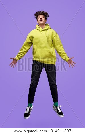 Full Body Modern Youngster In Casual Outfit Smiling And Looking At Camera While Jumping Against Purp