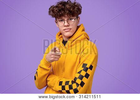 Serious Youngster With Curly Hair Wearing Nerdy Glasses And Yellow Hoodie And Pointing At Camera Whi