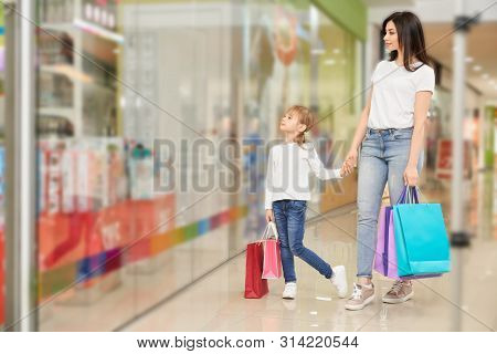 Family Shopping In Beautiful Shopping Center. Mother And Daughter Together Looking At Shop Window. Y