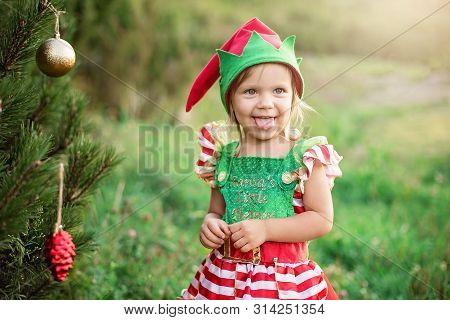 Child Waiting For A Christmas In Wood In Juli. Portrait Of Little Children Near Christmas Tree. Girl