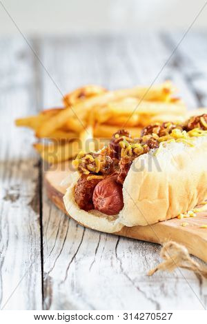 Hot Dog With Chilli, Cheddar Cheese And Mustard. Selective Focus With Blurred French Fries In The Ba
