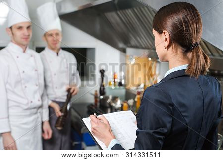 Restaurant Manager Briefing To His Kitchen Staff In The Commercial Kitchen.