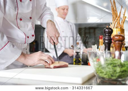 Chef Cutting Meat On Chopping Board, Professional Cook Holding Knife And Cutting Meat In Restaurant.