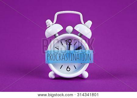Procrastination, delay and urgency concept. White alarm clock with text procrastination. poster