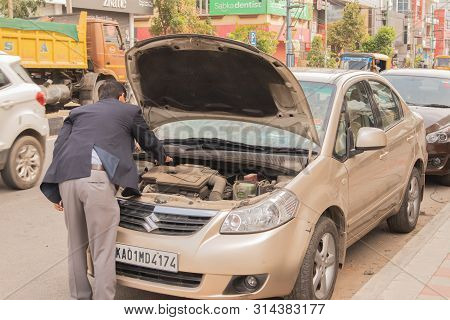 Bengaluru, India June 27, 2019 : Businessman Trying To Insepct His Broken Car On Road Side At Bengal
