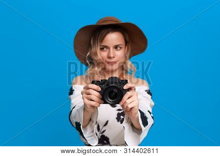 Portrait of a girl with curly blond hair in a sundown hat and white dress stands on a blue background. Model takes photos with retro camera. poster