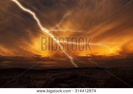 Lightning Striking Towards The Ground. Lightning During A Thunderstorm On A Sunset. Scenic Landscape