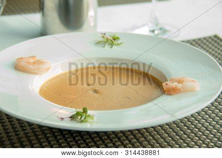 A Shrimp Soup Garnished With Fresh Shrimps