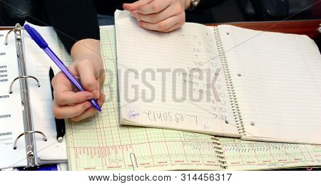 Teacher Grades Papers And Records It In Her Grade Book. She Is Holding A Purple Pen.