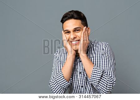 Unexpected Surprise. Young Cheerful Man Holding Face In Palms Over Gray Studio Background. Copy Space poster