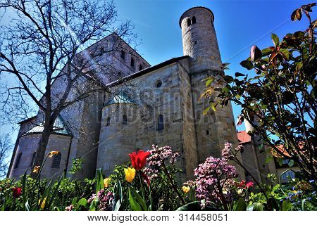 Tulips And Other Flowers In Front Of St. Michael's Church In Hildesheim