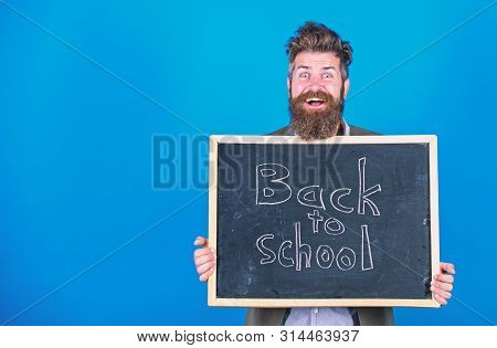 Teacher Bearded Man Stands And Holds Blackboard With Inscription Back To School Blue Background. Tea