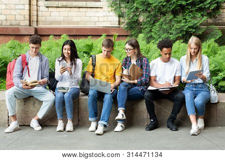 College Students Studying In University Campus With Books And Devices, Preparing For Exams