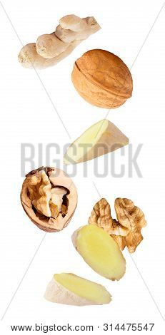 Floating Walnuts And Ginger Isolated On White Background
